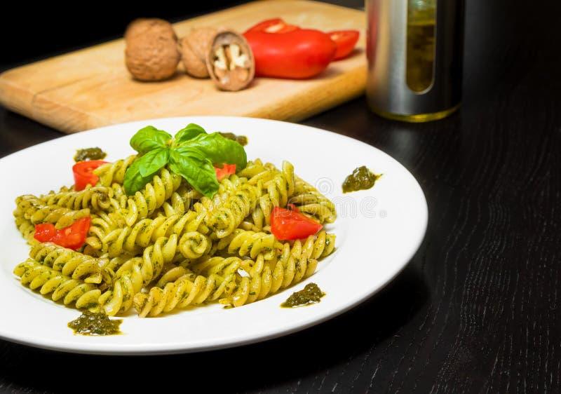 Maträtt av pasta med genovese sås och grönsaker för pesto, tomat och basilika på den svarta wood tabellen royaltyfria bilder
