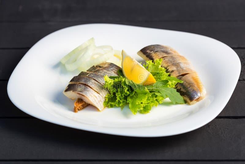 Maträtt av skivasillfisken med gräsplaner, citronen och löken royaltyfria bilder