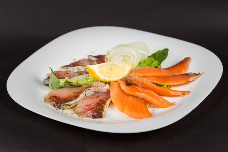 Maträtt av skivor vit och röd fiskfilé med citronen royaltyfria foton