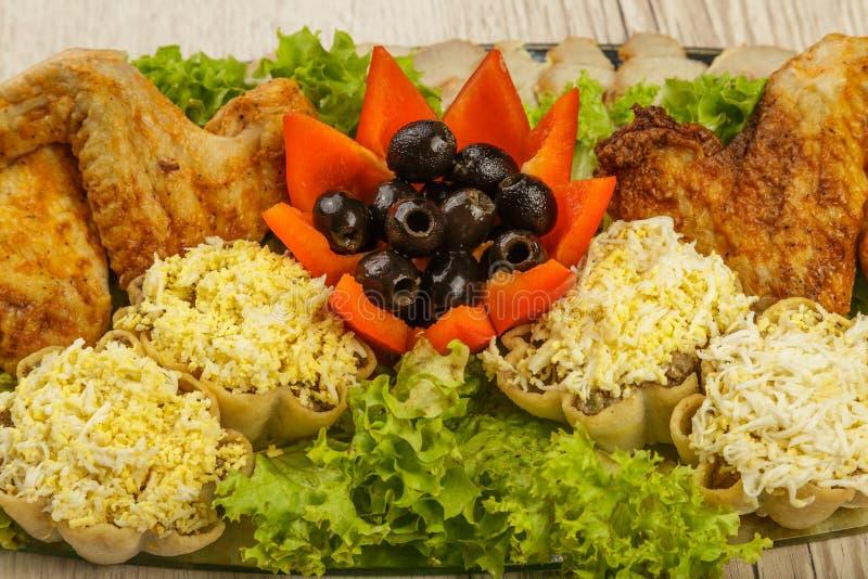 Maträtt från tartlets och fega vingar med närvaron av grönsallatsidor royaltyfri fotografi