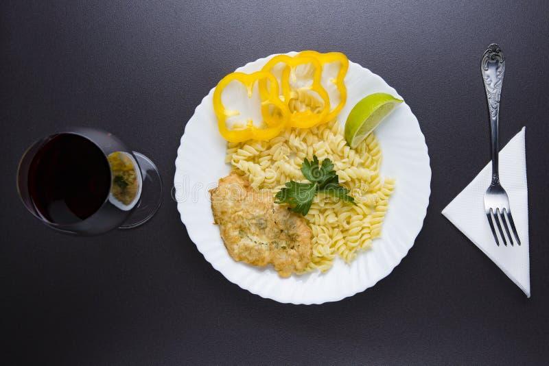 Maträtt i platta och exponeringsglas av rött vin över bästa sikt för matställe pasta och kotlett med skivor av gul peppar på port royaltyfria foton
