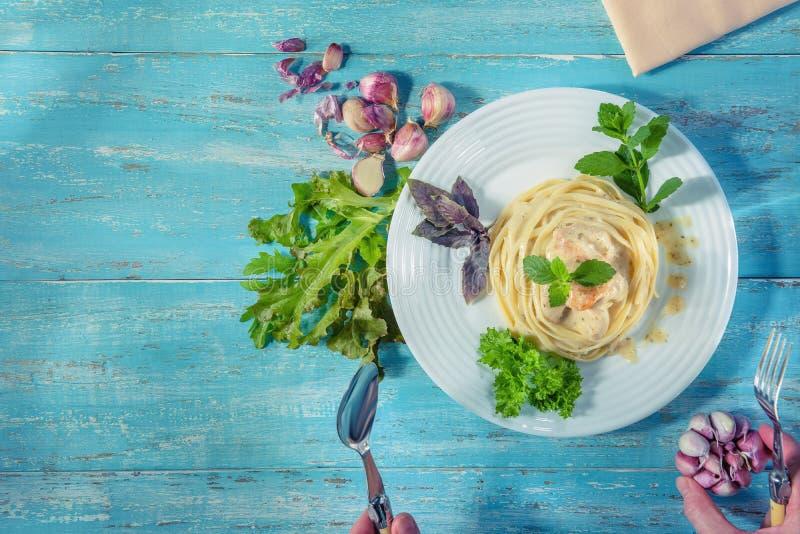 Maträtt med italiensk spagetti som står på en blå trätabell arkivbild
