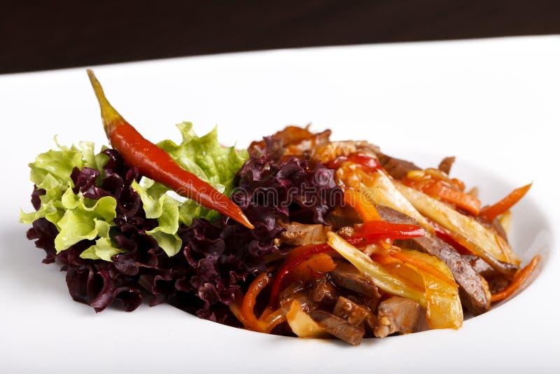 Maträtt med kött, potatisar och örter på en vit platta arkivfoton