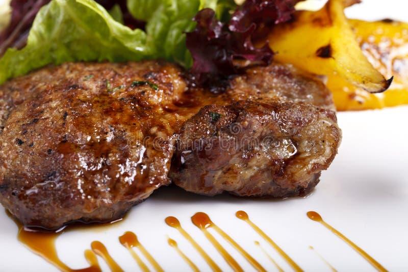 Maträtt med kött, potatisar och örter på en vit platta fotografering för bildbyråer