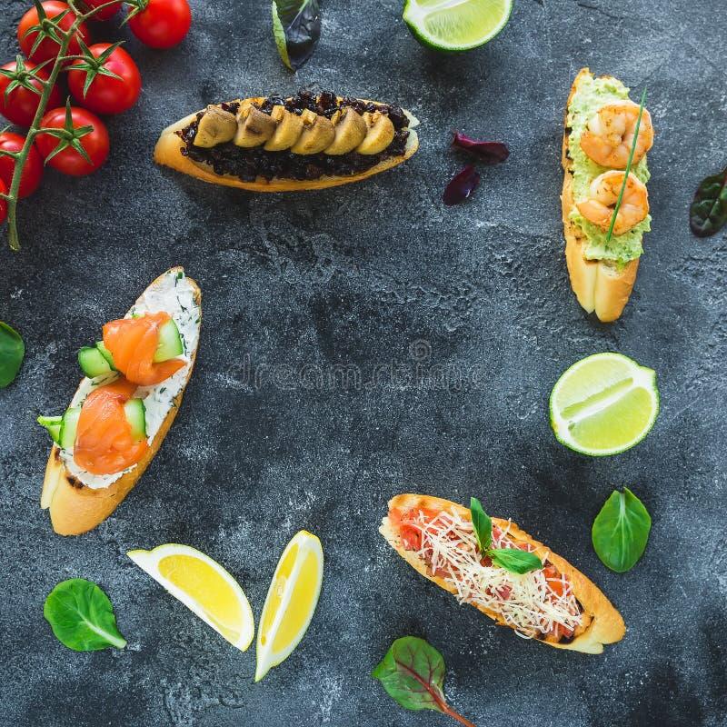 Matram av smörgåsar med räkan, laxen, champinjonen och limefrukter på mörk bakgrund höna stekt ben royaltyfri foto