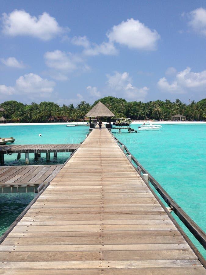 Matraquez Med Kani, longue jetée entourée par la mer verte, avec des huttes dans la distance image libre de droits