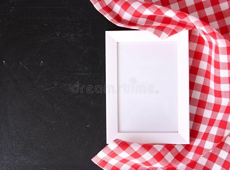Matreceptmall Rutig torkduk på svart tavla arkivbild