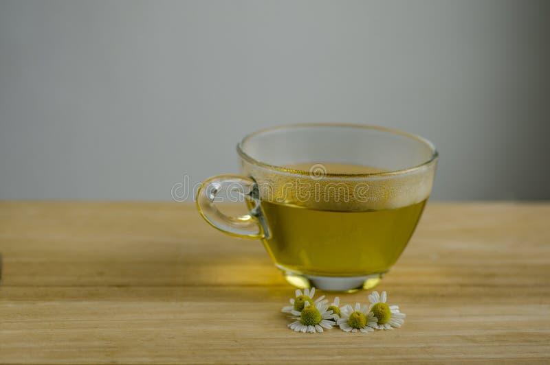 Matricaria chamomilla Blumen und trasparent Tasse Tee auf Holztisch, Kräutermedizin neuen Blühens lizenzfreies stockfoto
