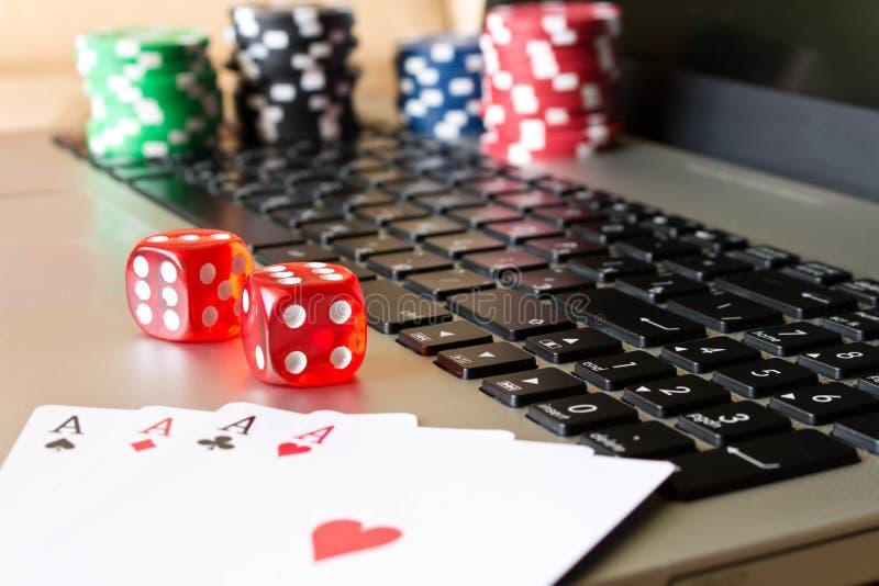 Matrices, jetons de poker et cartes de jouer sur l'ordinateur portable Le concept de dessus photographie stock