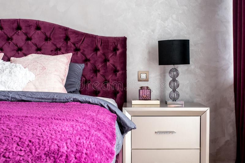 Matrimonial double bed in elegant and comfortable modern bedroom with nightstand lamp closeup. Interior design details stock image