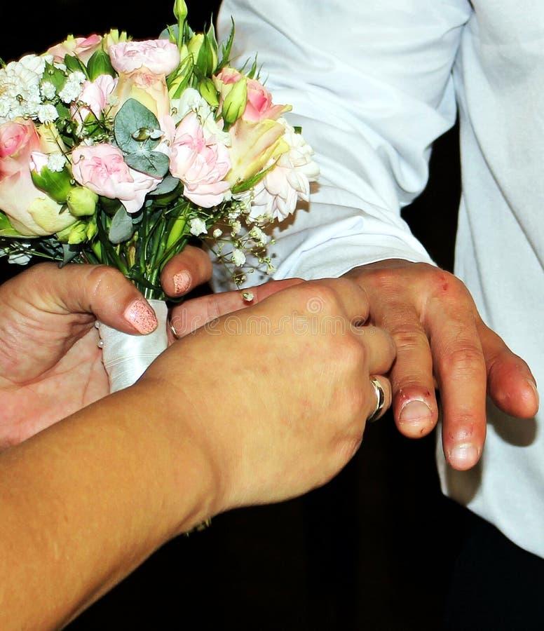 Matrimonio insertando un anillo de bodas en un finger fotografía de archivo libre de regalías