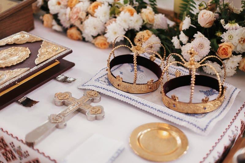 Matrimonio santo en iglesia Coronas, cruz, biblia y velas de oro foto de archivo libre de regalías