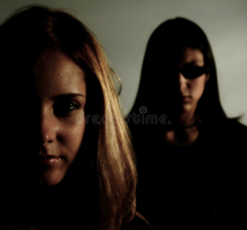 Matrix girls. Attractive young girls posing in a Matrix like atmosphere royalty free stock images