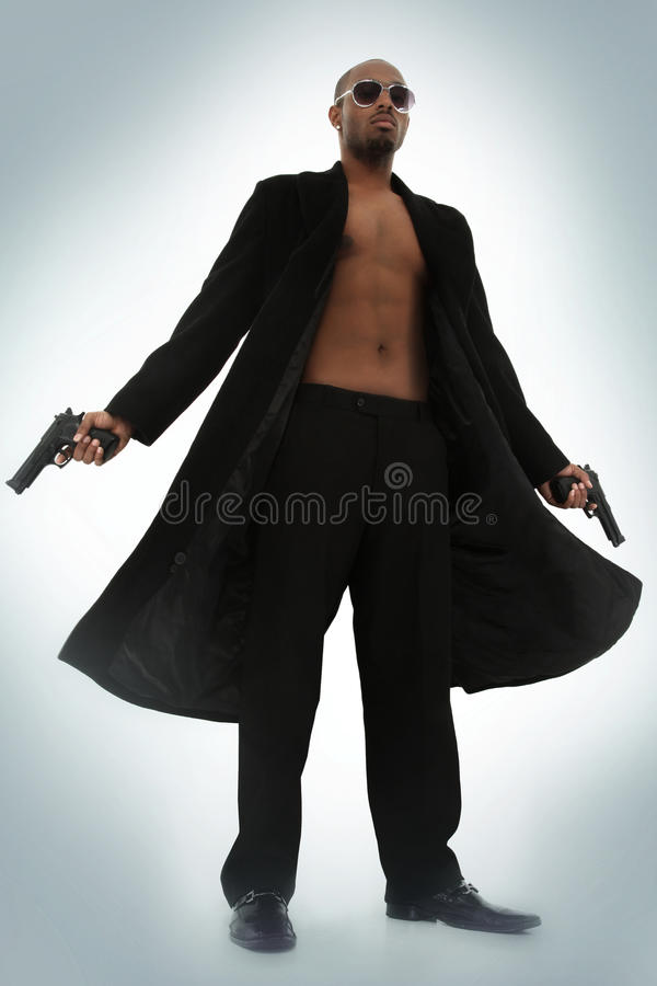 Matrix Style Role Play Character Adult Man. In Trench Coat with Pistols over blue foggy background royalty free stock photography