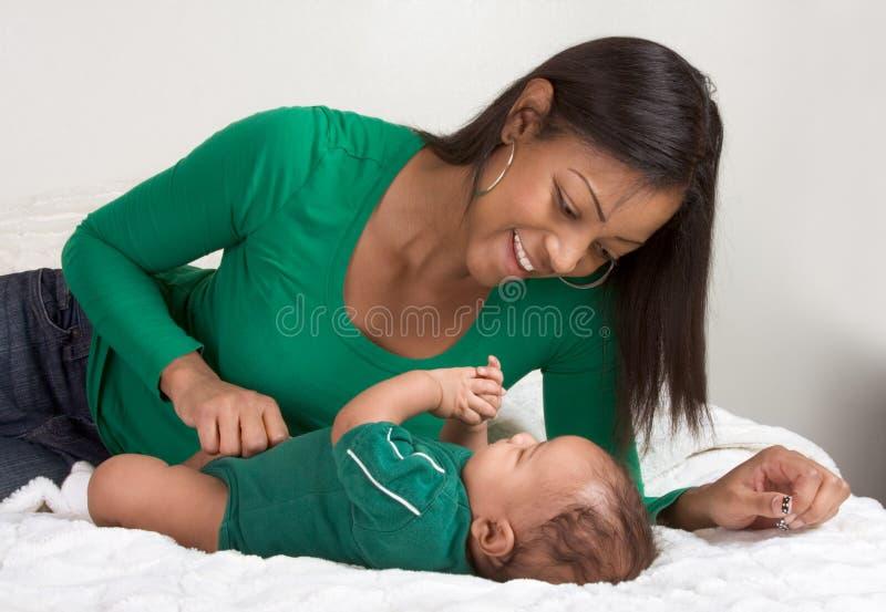 Matriz étnica que joga com seu filho do bebé na cama fotos de stock