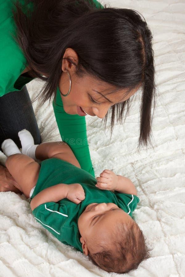 Matriz étnica que joga com seu filho do bebé na cama fotografia de stock royalty free