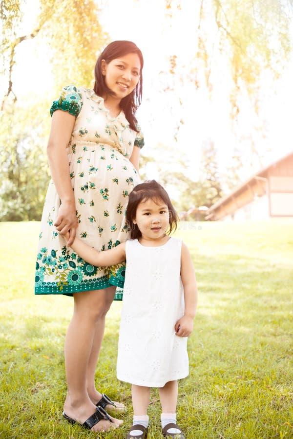 Matriz asiática grávida e sua filha imagens de stock