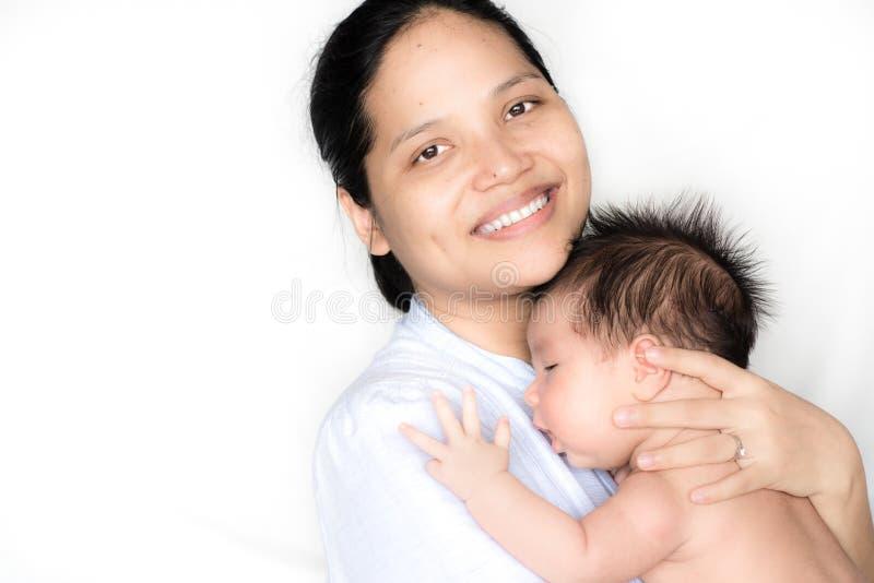 A matriz asiática prende seu bebê recém-nascido fotos de stock royalty free