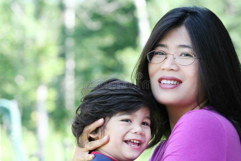 Matriz asiática que guardara lovingly seu filho foto de stock royalty free