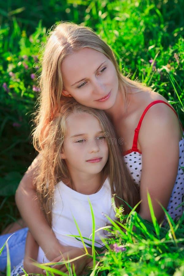 Matriz bonita e filha que sentam-se no prado fotografia de stock