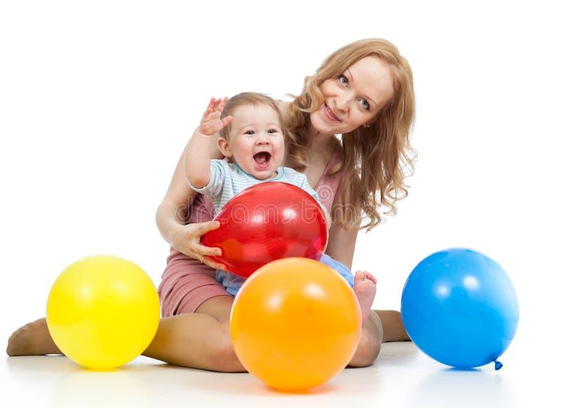 Matriz bonito e bebê com os balões que têm o divertimento imagem de stock royalty free