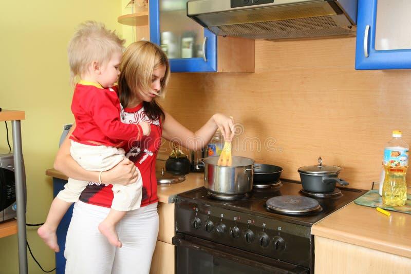 Matriz com a criança na cozinha imagens de stock