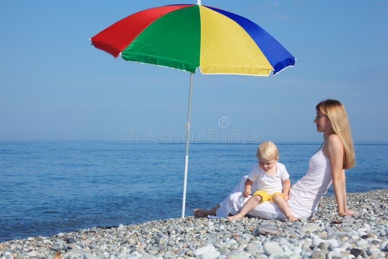 Matriz com a criança sob o guarda-chuva em Pebble Beach imagem de stock