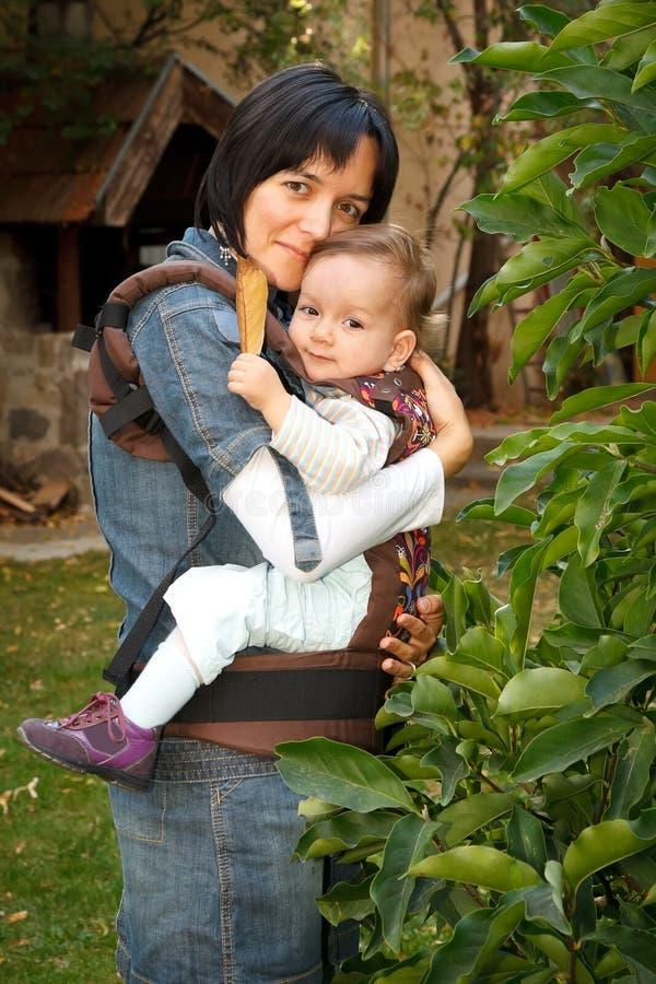 Matriz com o bebê no estilingue fotos de stock royalty free