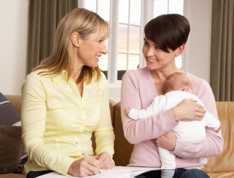 Matriz com o bebê que fala com visitante da saúde imagens de stock
