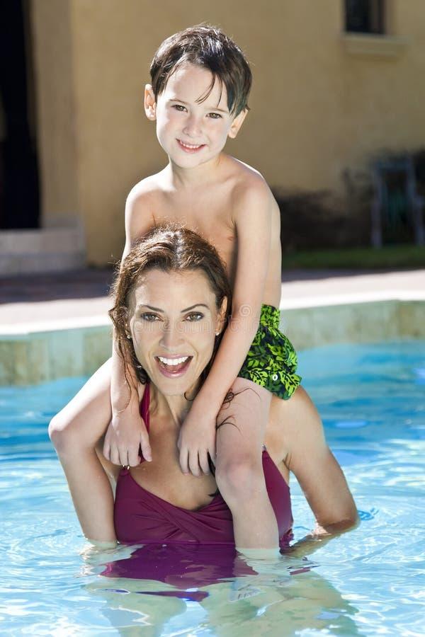 Matriz com o filho em seus ombros na piscina imagem de stock