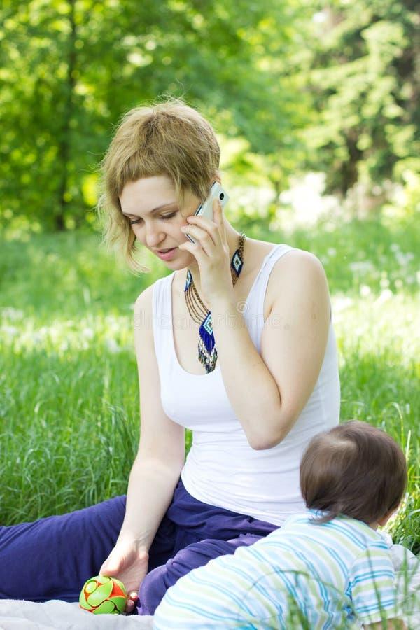Matriz com o relaxamento do filho ao ar livre fotografia de stock royalty free