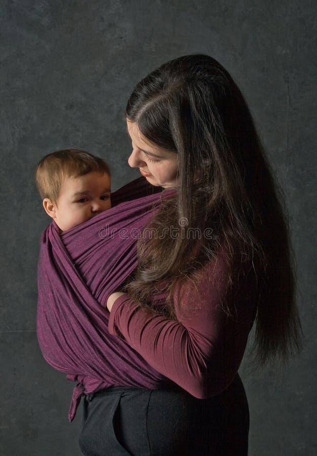 Matriz com sua filha no estilingue imagem de stock