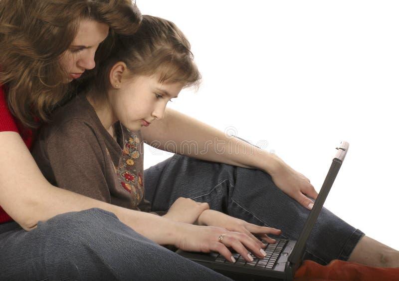 Matriz com trabalho da filha no computador fotografia de stock royalty free