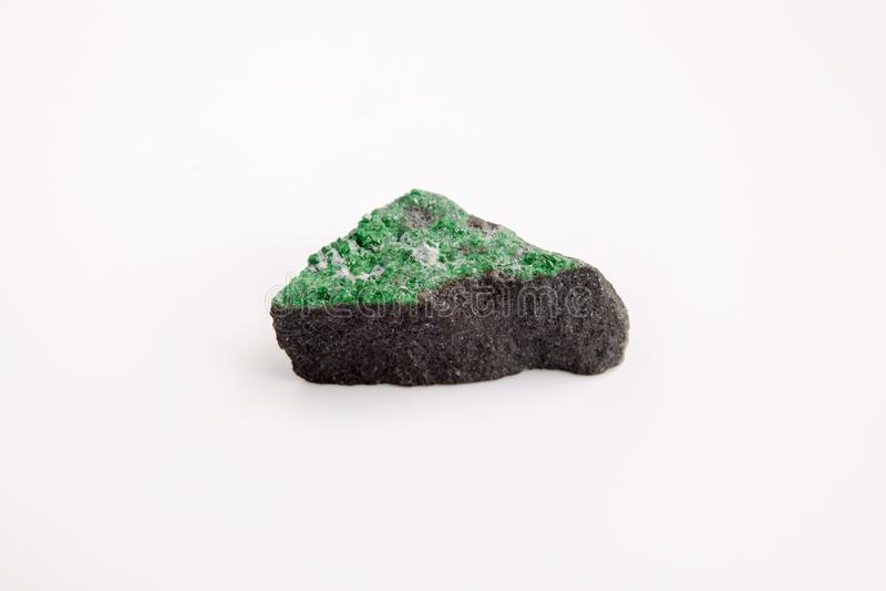 Matriz de cristais de Uvarovite na rocha áspera no fundo branco foto de stock royalty free