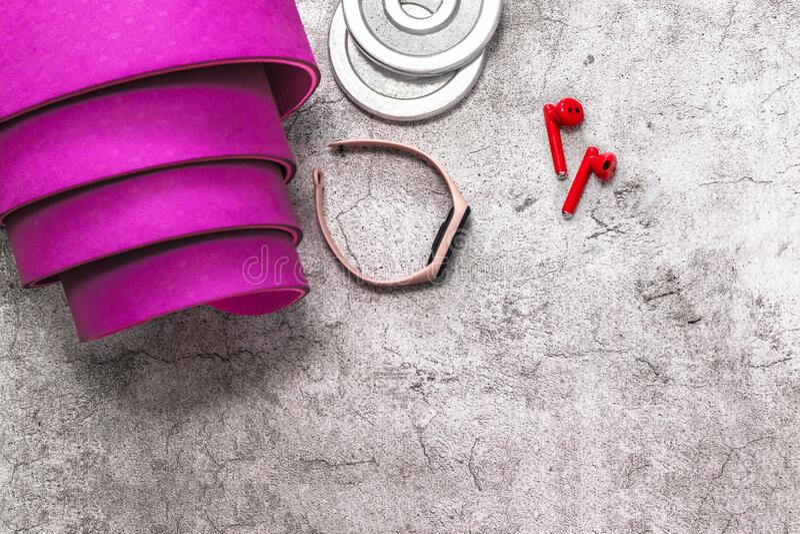 Matriz de ioga de borracha roxa, fones de ouvido, peso de halterofone, rastreador de qualidade para treinamento em fundo cinza co fotos de stock