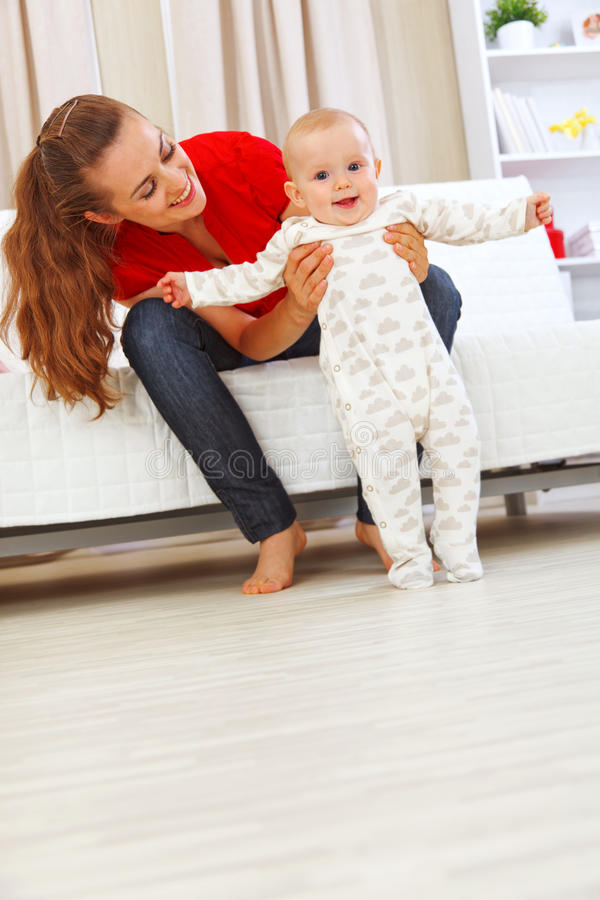 A matriz de sorriso que ajuda o bebê alegre aprende andar fotos de stock