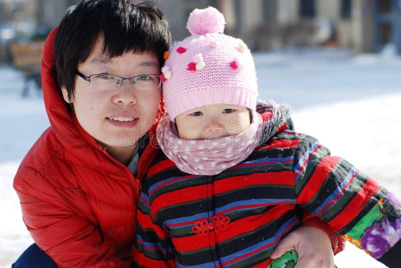 Matriz e bebê a jogar na neve fotos de stock royalty free