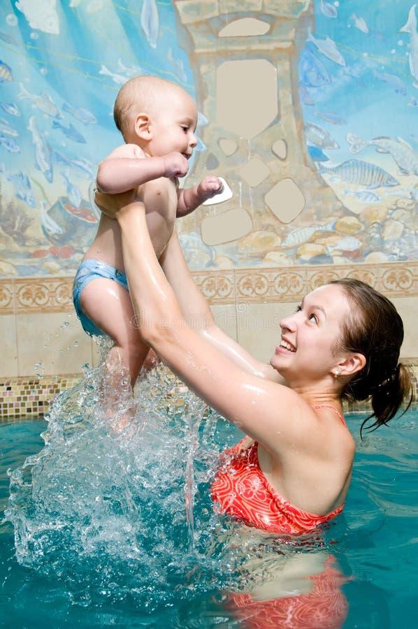 Matriz e bebê na piscina foto de stock