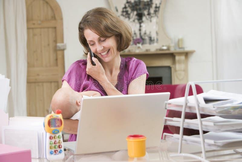 Matriz e bebê no escritório home com portátil fotografia de stock royalty free