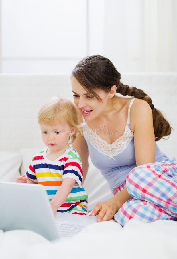 Matriz e bebê novos modernos que usa o portátil fotos de stock