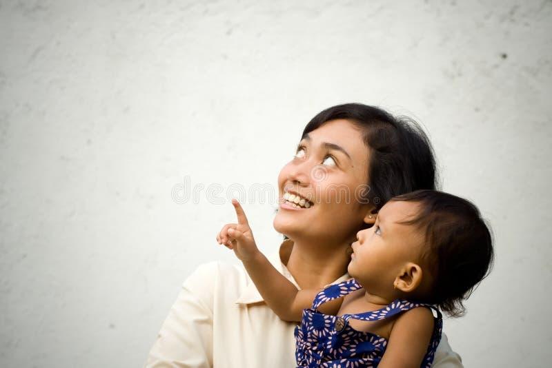 Matriz e bebê que olham acima e que apontam foto de stock royalty free