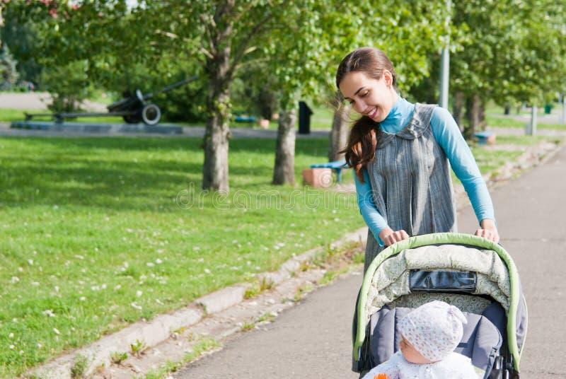 A matriz e a criança andam no parque imagens de stock