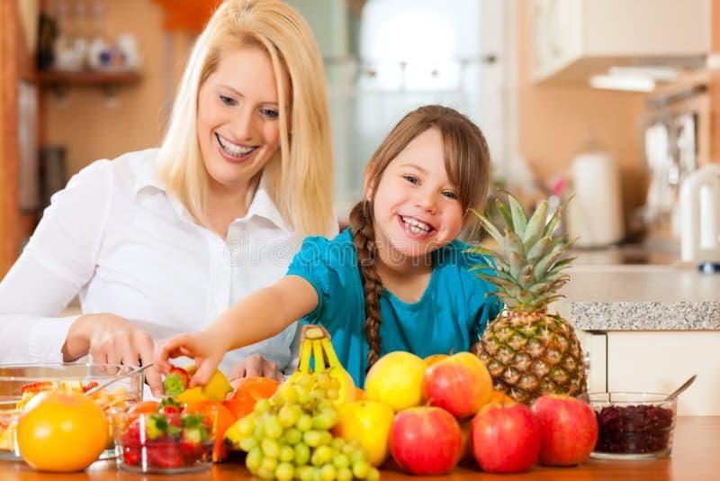 Matriz e criança com lotes das frutas foto de stock