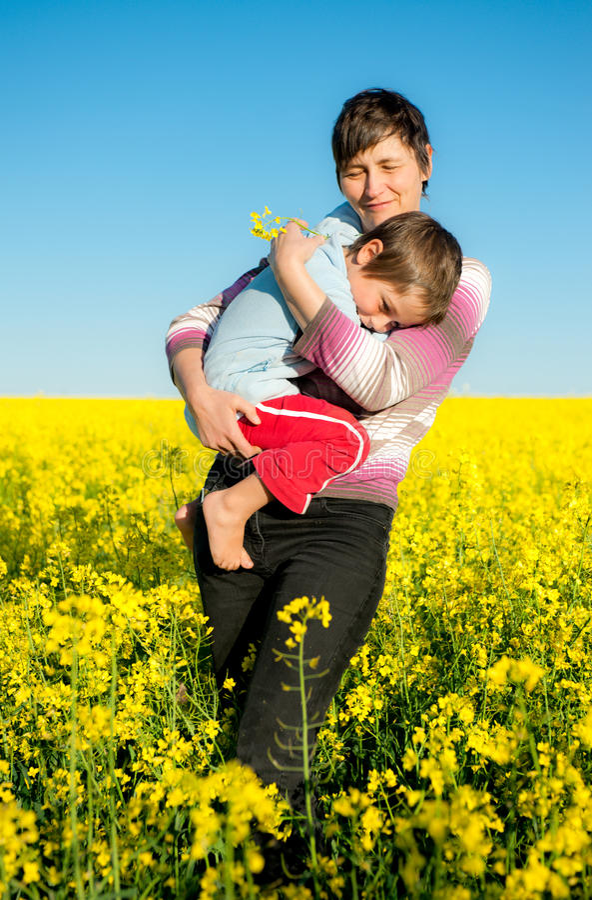 Matriz e criança em um campo do rapeseed fotografia de stock