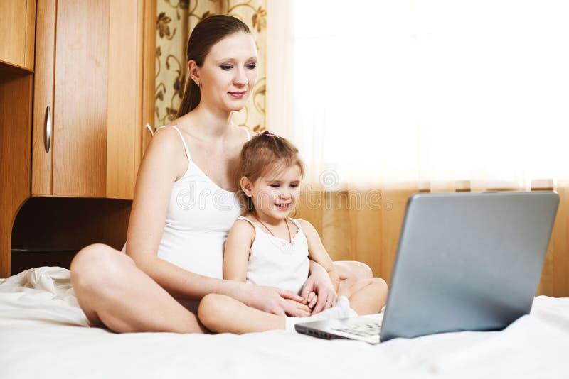 Matriz e criança grávidas felizes com portátil foto de stock royalty free