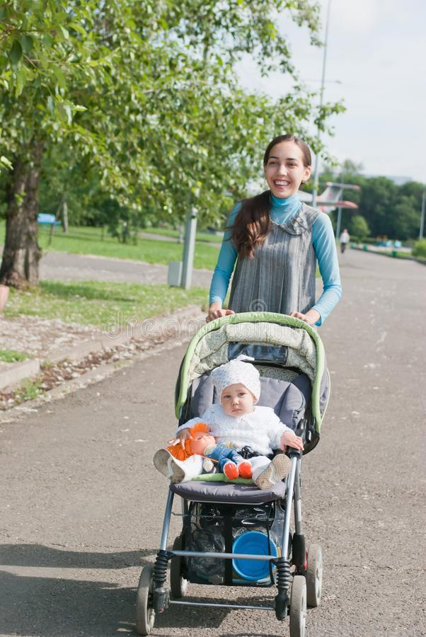 A matriz e a criança no carrinho de criança andam no parque fotografia de stock