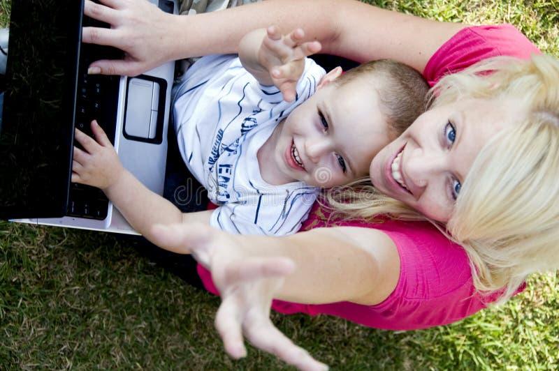 Matriz e criança que trabalham junto no portátil imagens de stock royalty free