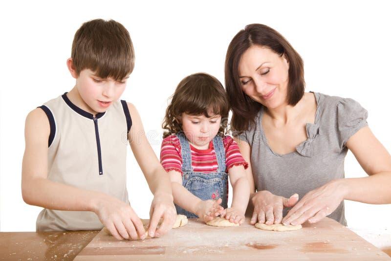 Matriz e crianças na cozinha que faz uma massa de pão foto de stock