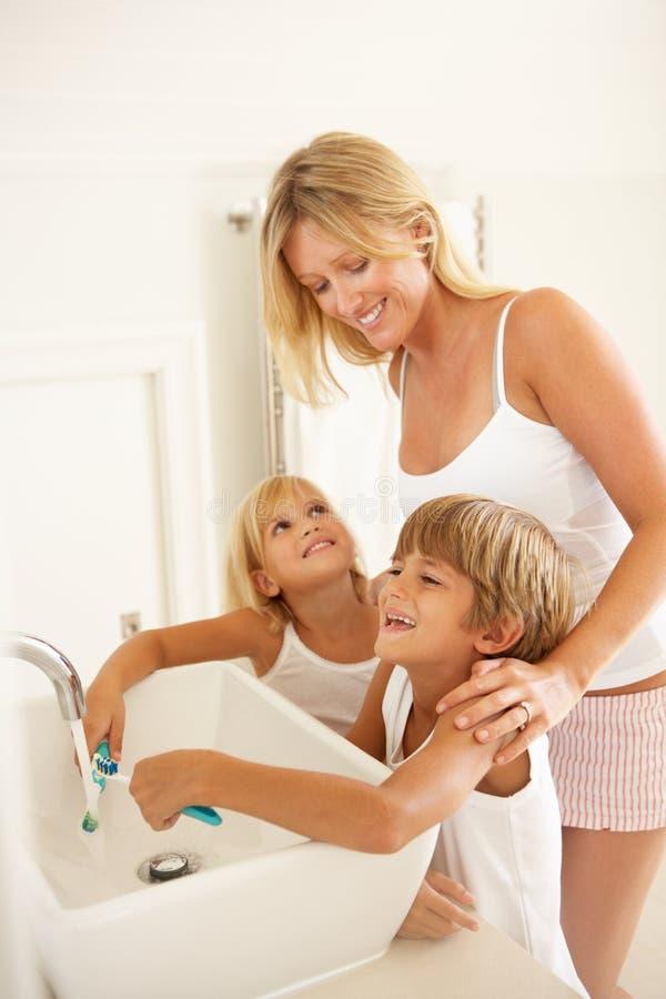 Matriz e crianças que escovam os dentes no banheiro fotografia de stock