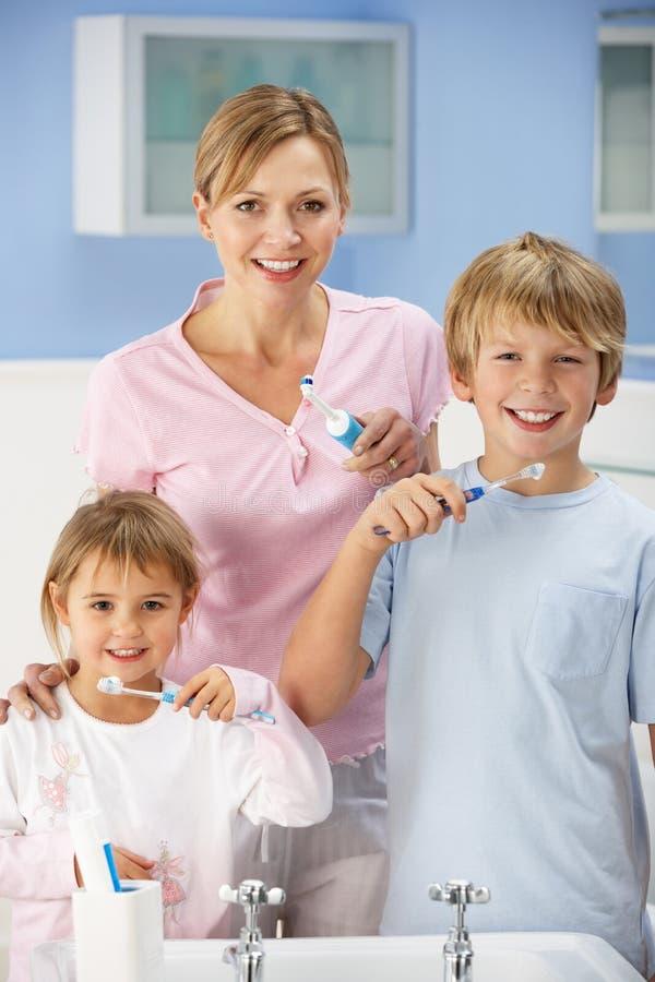 Matriz e crianças que limpam os dentes no banheiro fotografia de stock